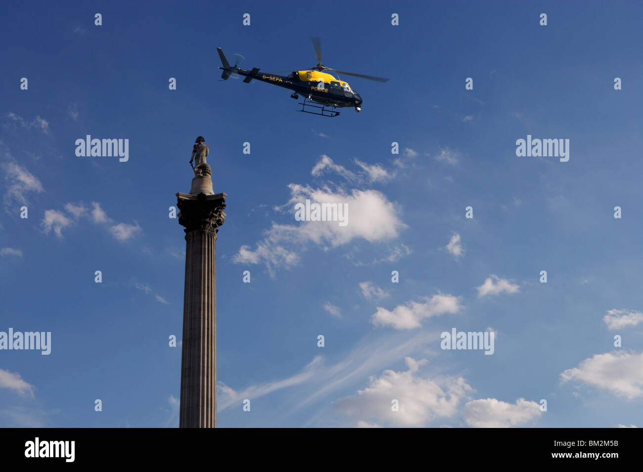 Nelsons Column and police helicopter, London, UK - Stock Image