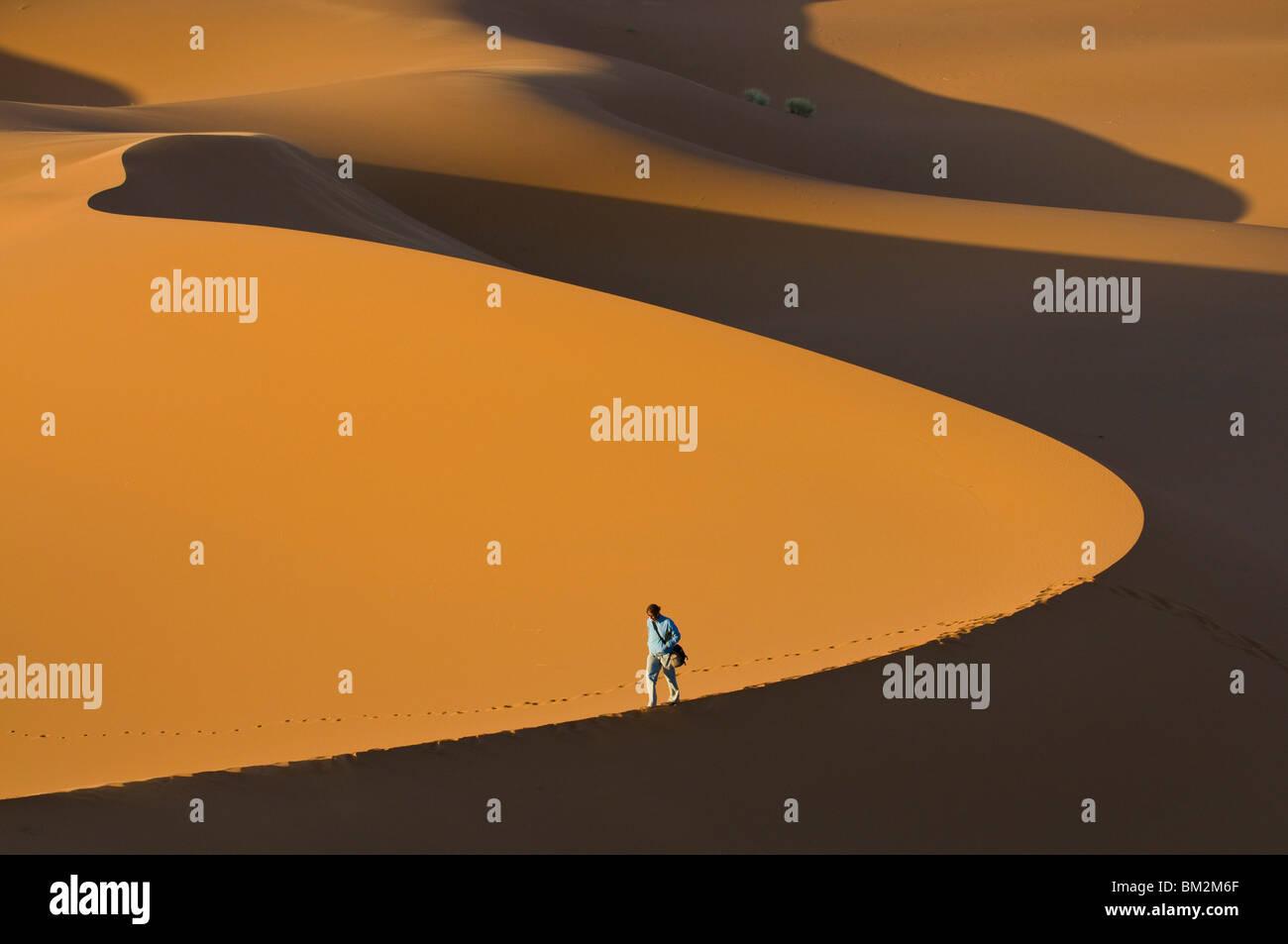 Tourist walking along a giant sand dune, Merzouga, Morocco - Stock Image
