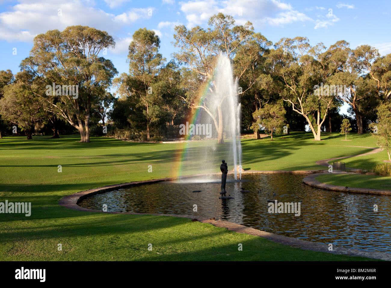 Fountain and landscaped lawns in Kings Park, Perth, Western Australia. A rainbow appears in the fountain's spray. - Stock Image