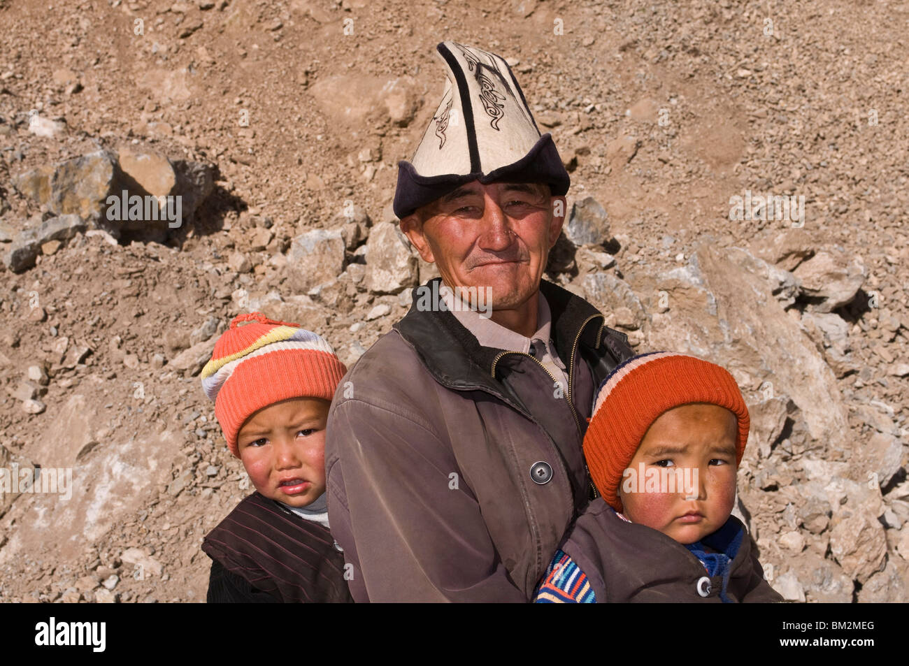 Man with twins in the mountains near Sary Tash, Kyrgyzstan Stock Photo