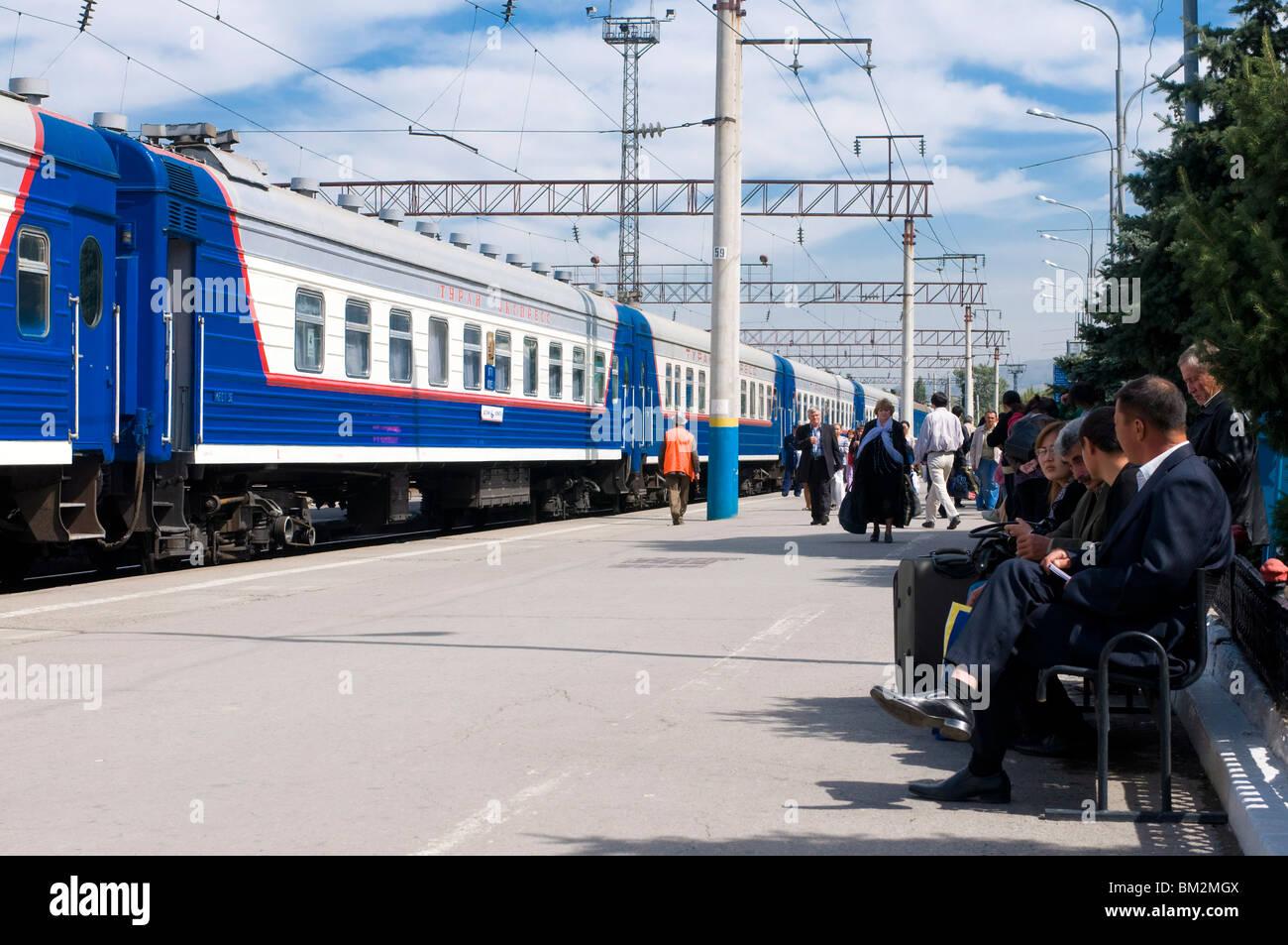 Railway station with passengers and train, Almaty, Kazakhstan - Stock Image