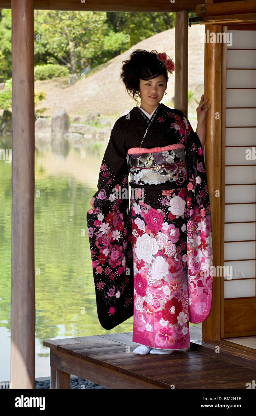 A 20-year old Japanese girl wearing spring furisode kimono with long sleeves to indicate her single social status, - Stock Image