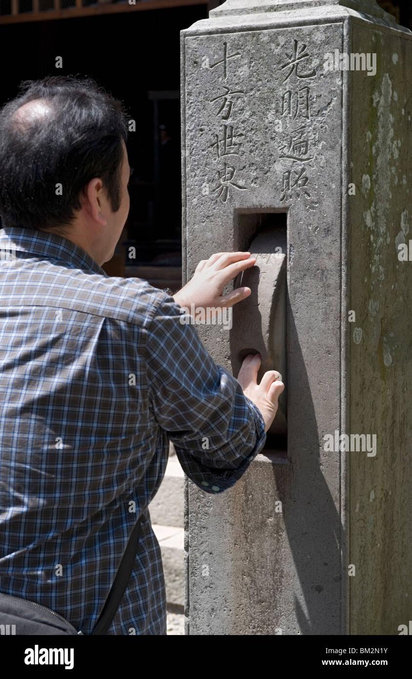 Man spinning a prayer wheel at Zenkoji Temple, Nagano City, Japan - Stock Image