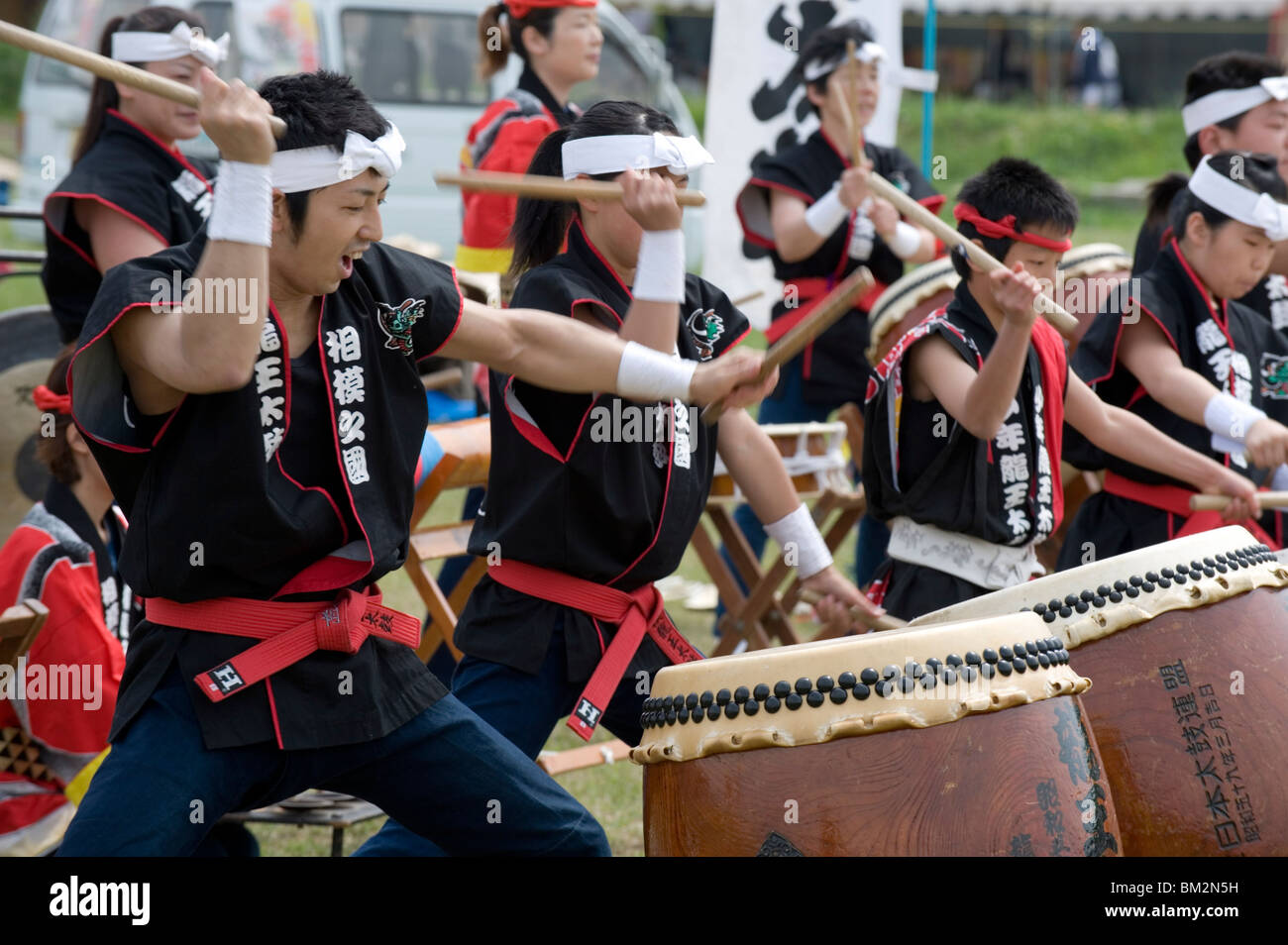 Energetic group of drummers beating Japanese taiko drums during an outdoor performance, Japan - Stock Image