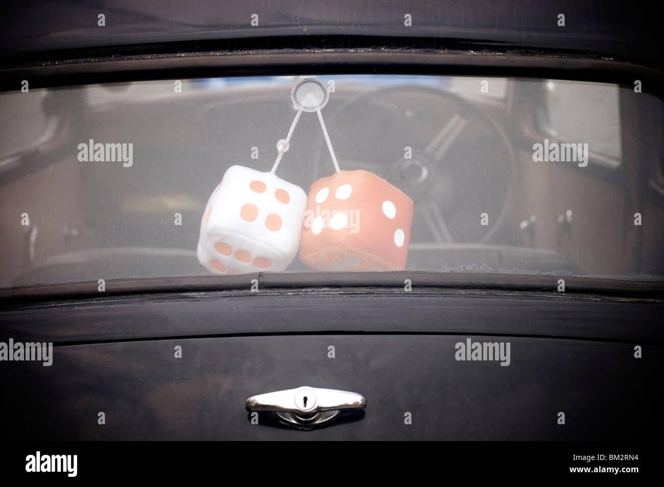 Furry dice in rear window of Austin Prefect car. - Stock Image