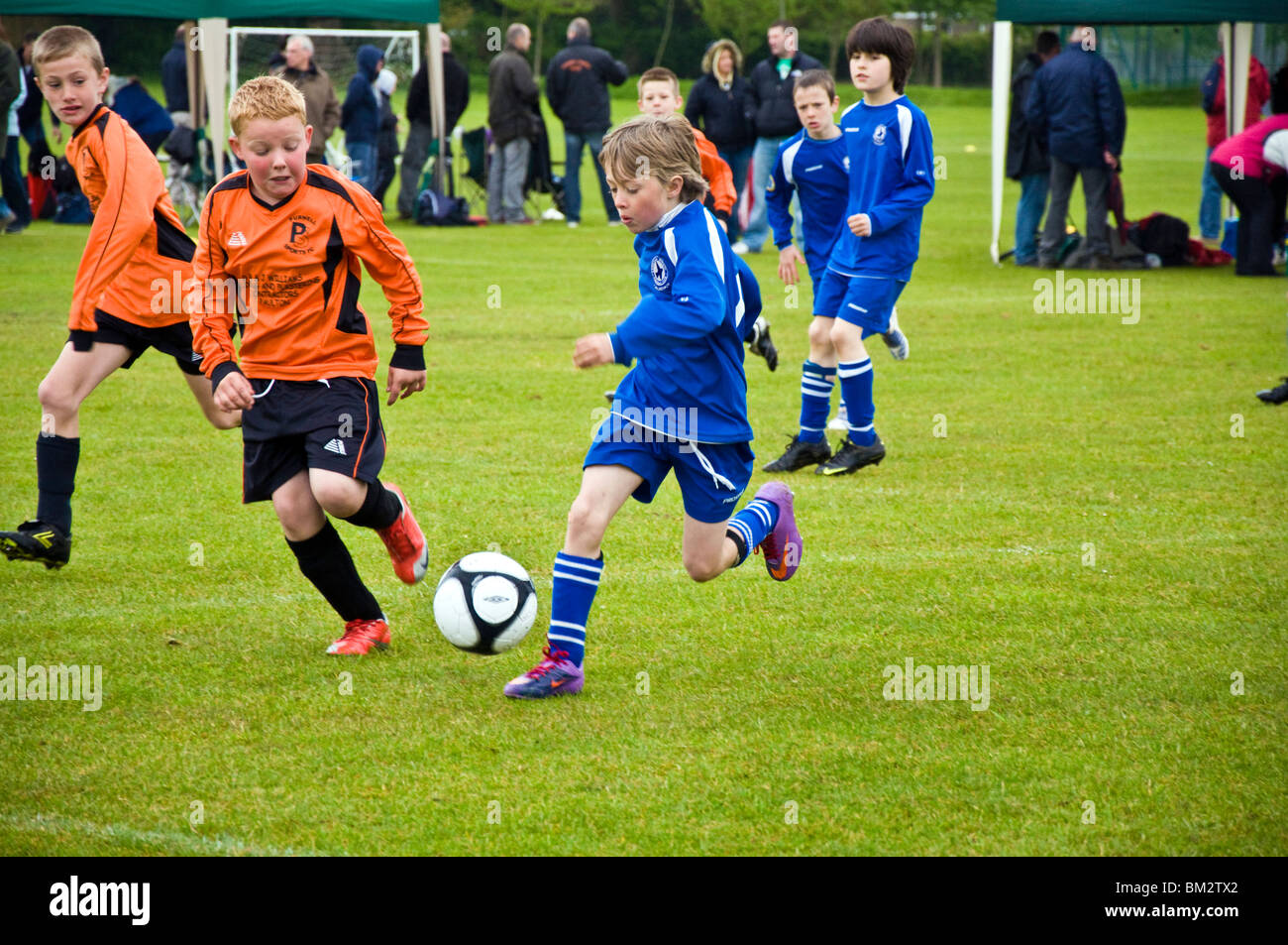 Under 10s Football Tournament Larkhall in blue and Purnels in orange Benny Wayman on the ball - Stock Image