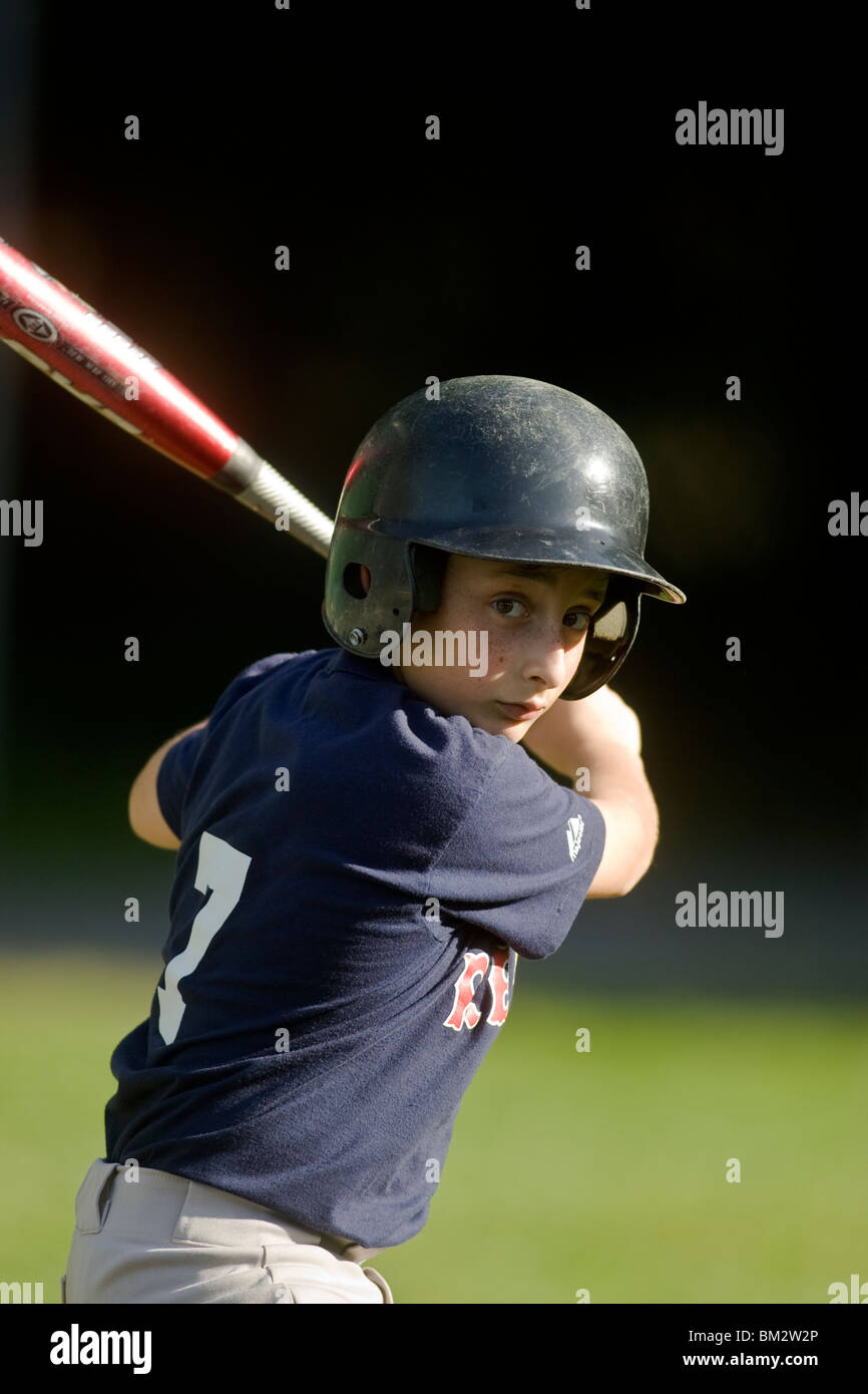 10 year old boy batting during little league baseball game. - Stock Image