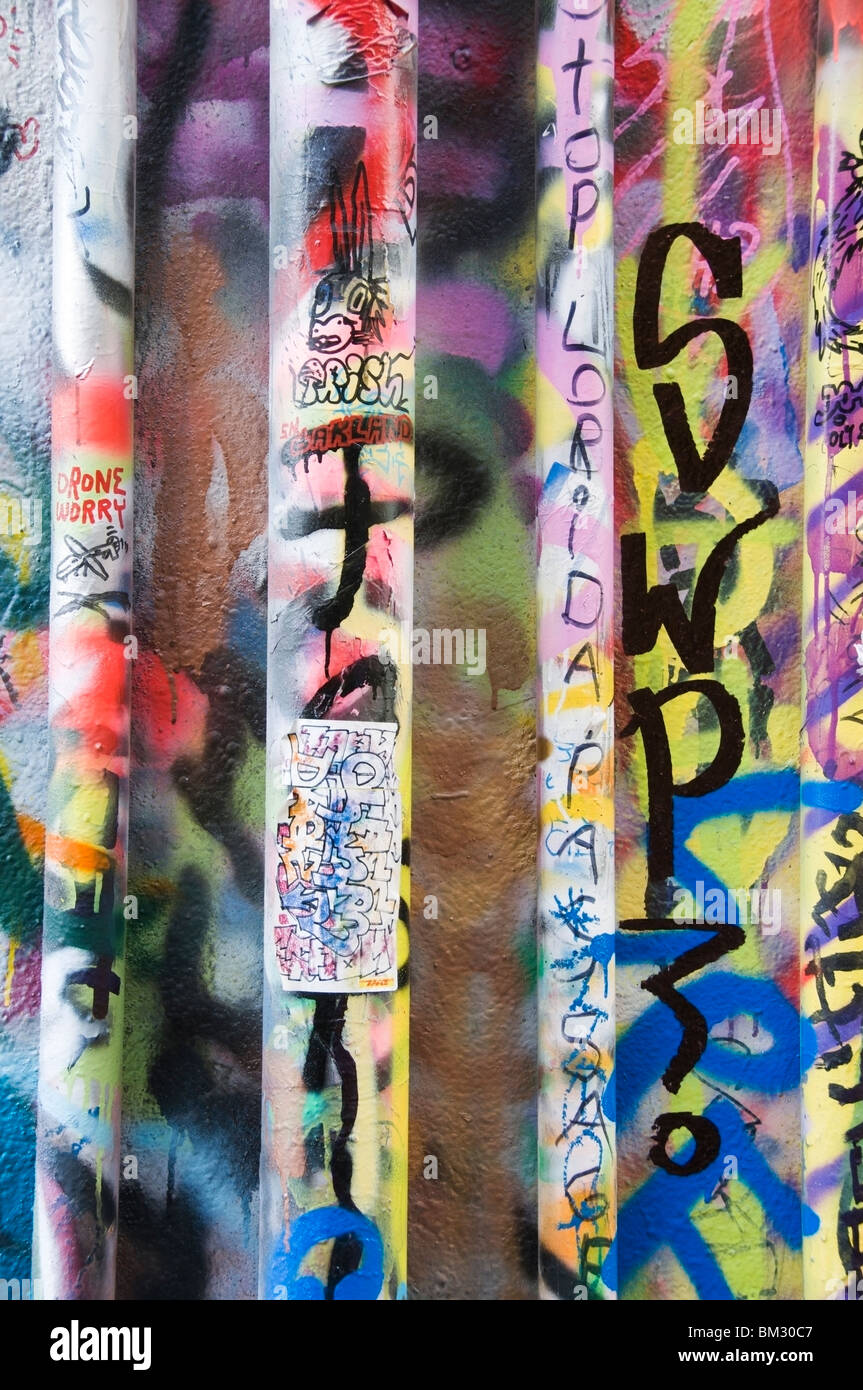 Graffiti on pipes and wall behind building in downtown Olympia, Washington. - Stock Image