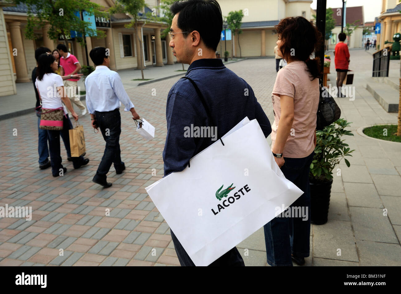 e25cfe4eb Chinese man carrying LACOSTE shopping bag at Beijing Scitech Premium Outlet  Mall in Beijing