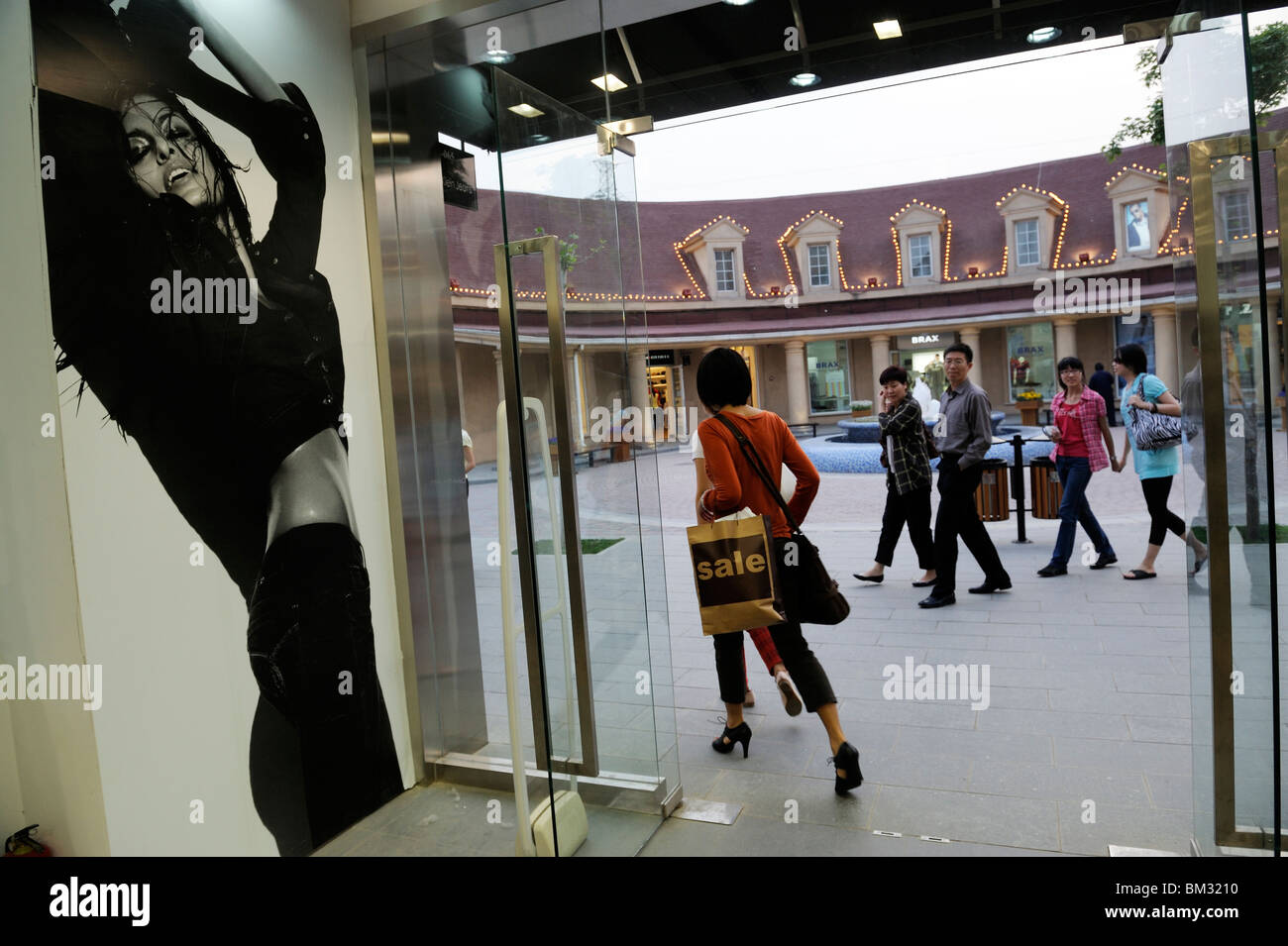 ba27f4915 A Chinese lady leaves Calvin Klein Jeans store after shopping at Beijing  Scitech Premium Outlet Mall