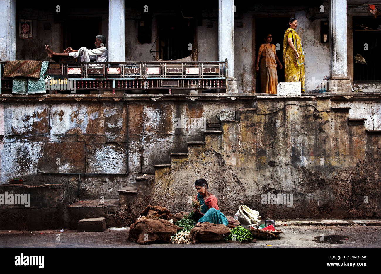 INDIA, MAY 12, 2010: A vegetable seller sits on the road outside an old house in Ahmedabad,Gujurat,India. - Stock Image