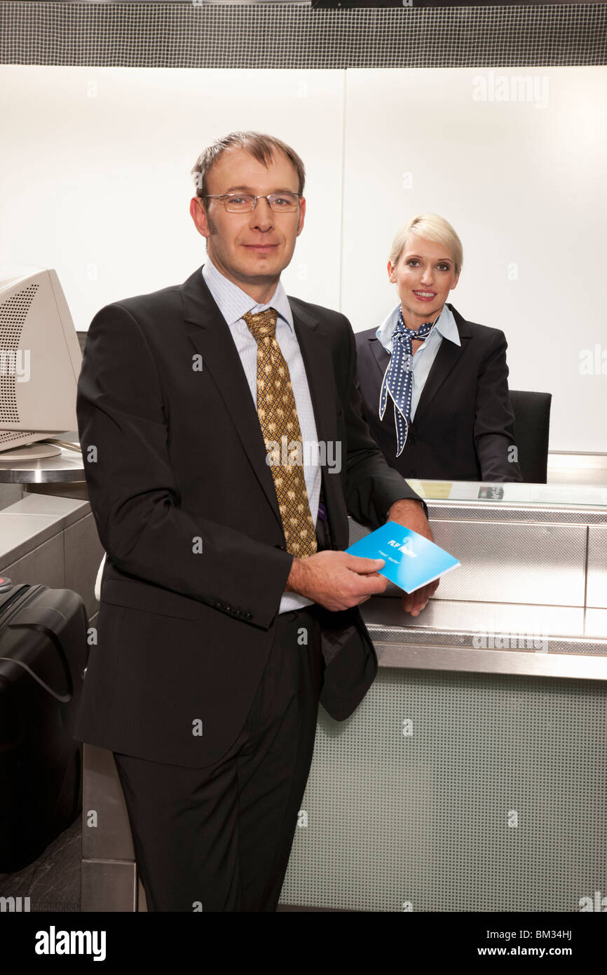 Businessman in front of checkin desk - Stock Image