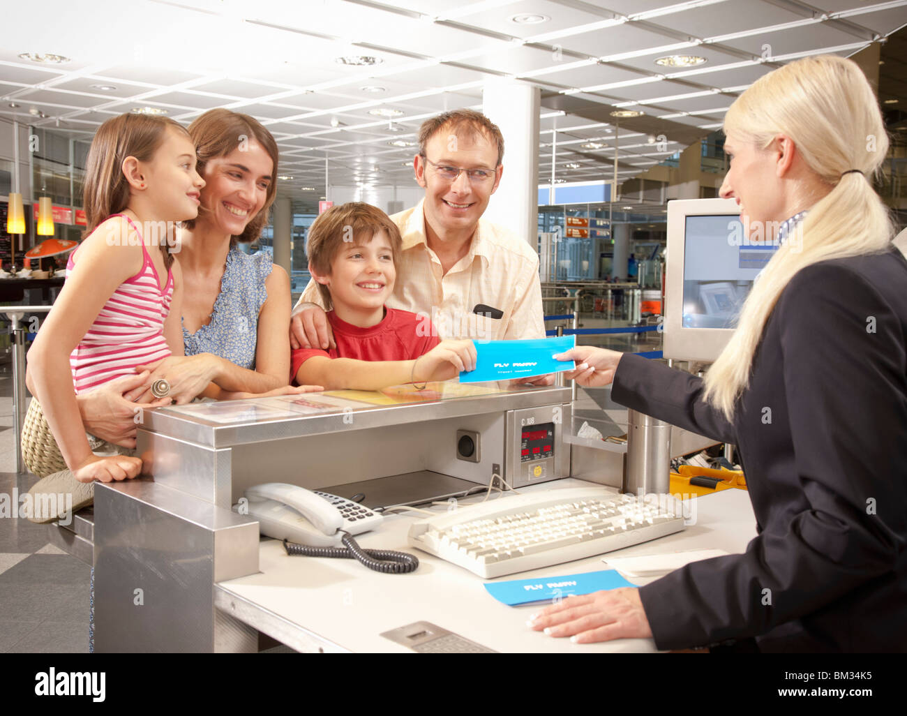 Family checking at the airport desk - Stock Image