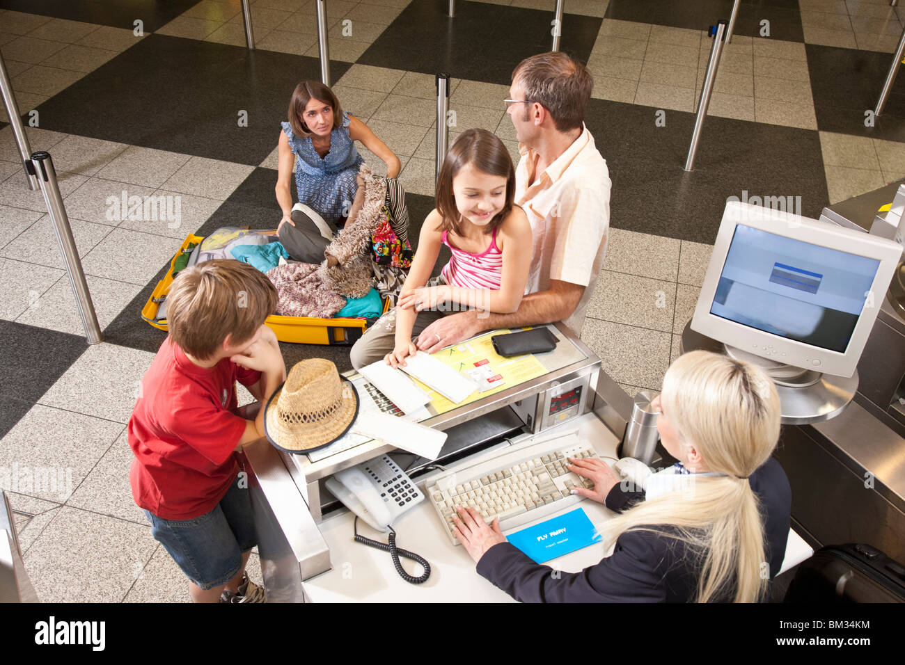 Mother checkin suitcase for vouchers - Stock Image