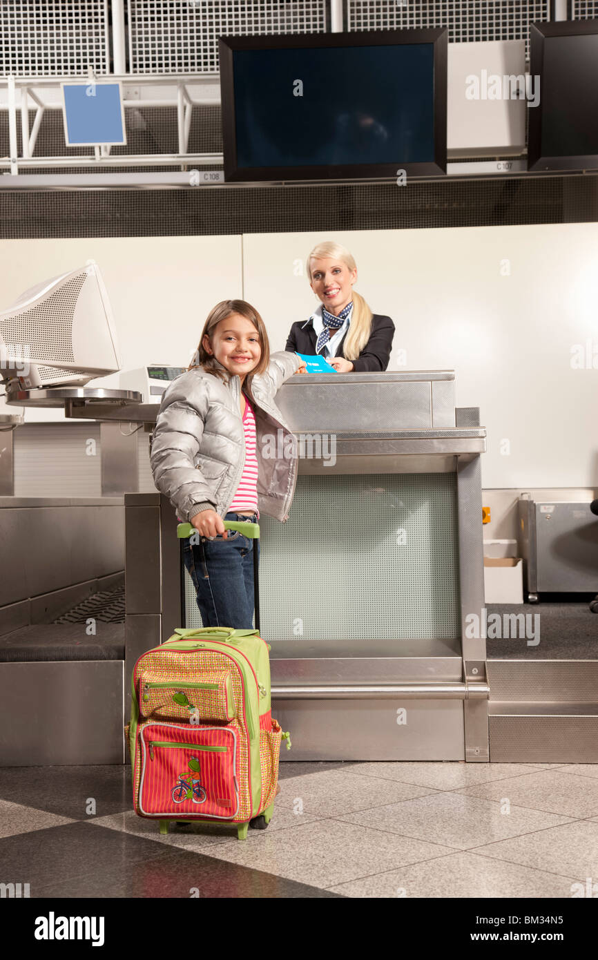 Young girl checkin in for her flight - Stock Image