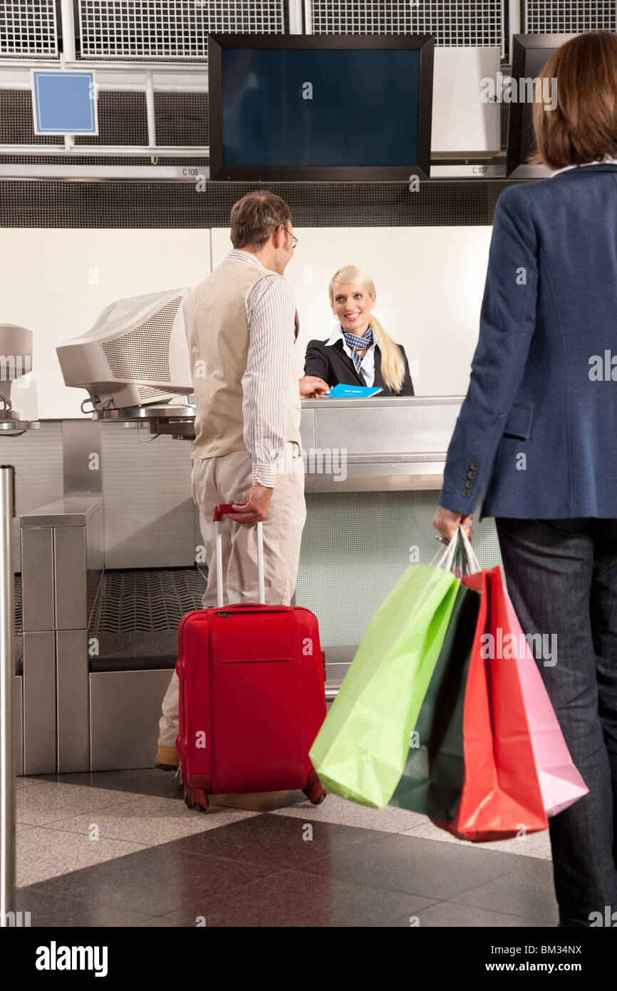 A couple checking in with shopping bags - Stock Image