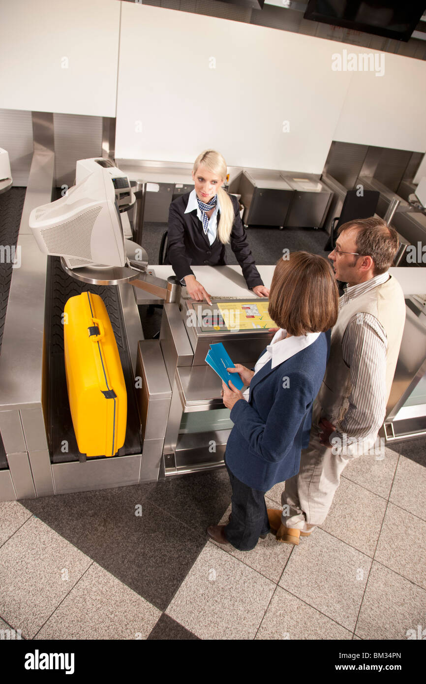 Lady checking the weight of a suitcase - Stock Image