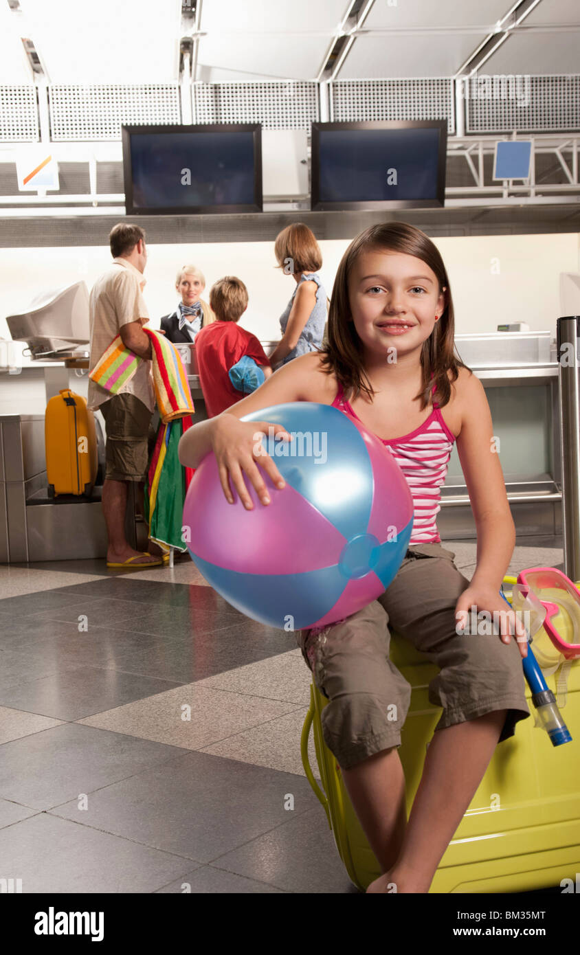 Little girl sitting on a suitcase Stock Photo