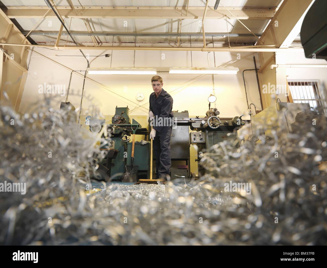 Apprentice Engineer Sweeping Swarf - Stock Image