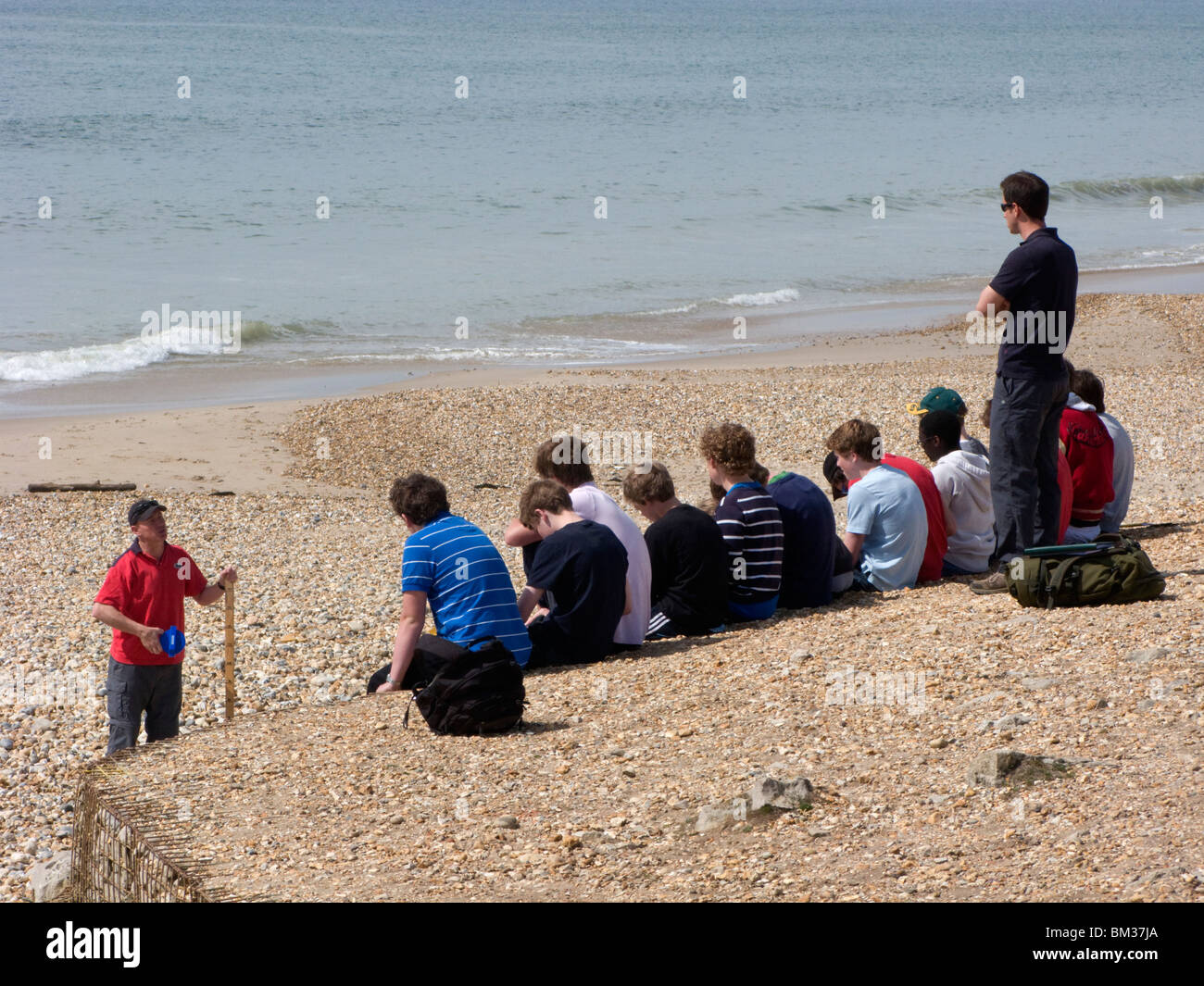 Students class outdoor lesson on beach with tutor, Southbourne, Bournemouth, Dorset, UK - Stock Image