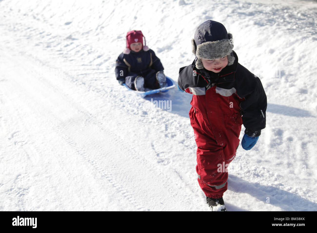 Two siblings babies kids children play together snow sledge boy girl pull pulling model released - Stock Image