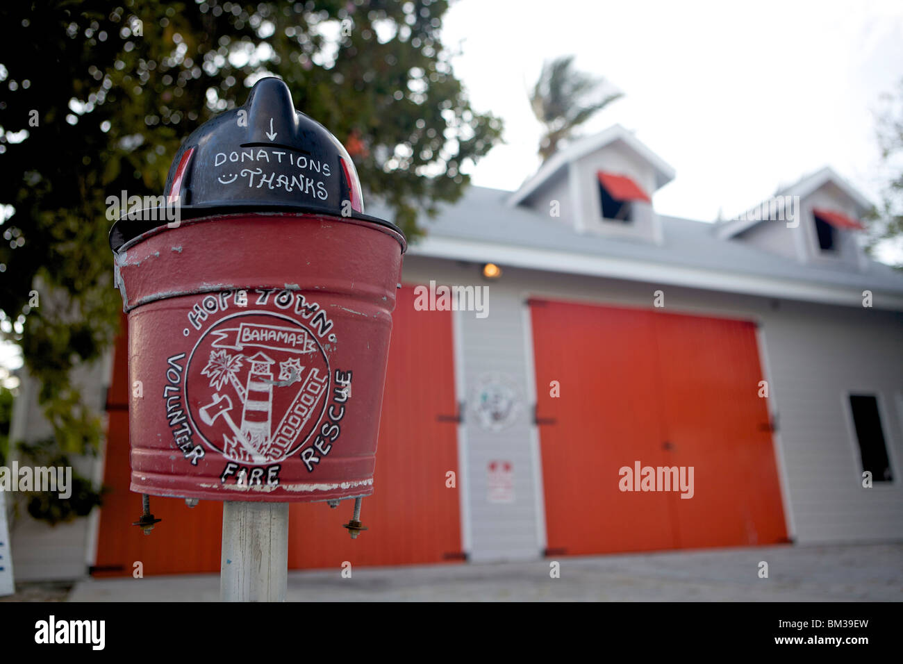 Donation tin for the Hope Town volunteer fire department situated outside the Fire Station in Hope Town in the Bahamas. - Stock Image