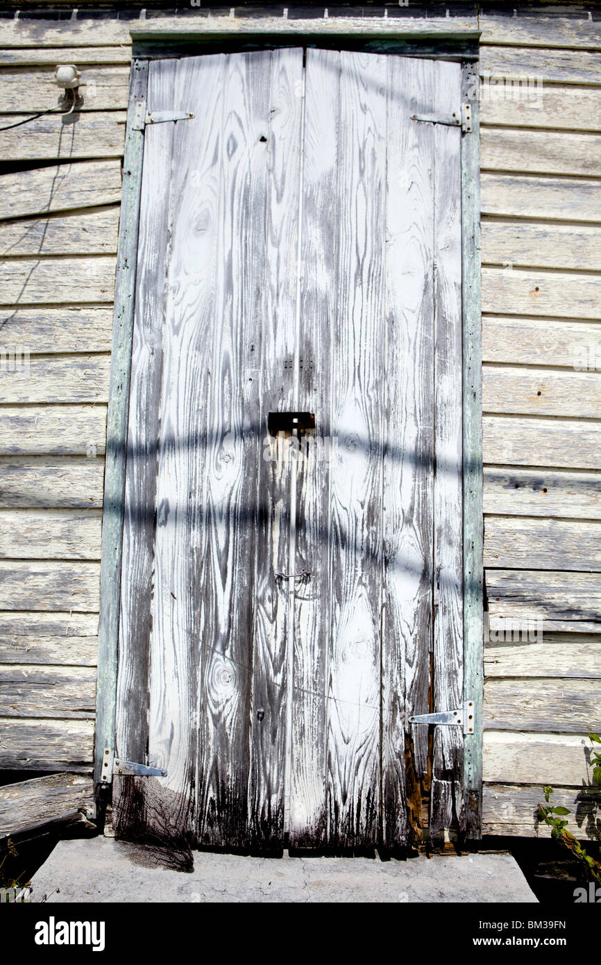 A weather worn, distressed wooden door in white wash Stock Photo