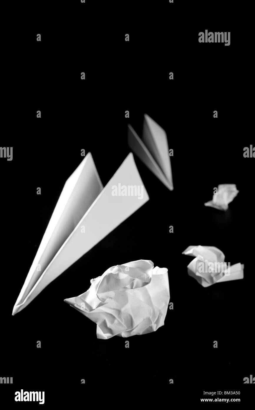 Trash paper and air plane, bored in the office metaphor, over black - Stock Image