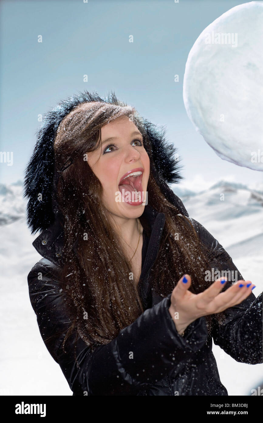 Young woman laughs at giant snowball - Stock Image