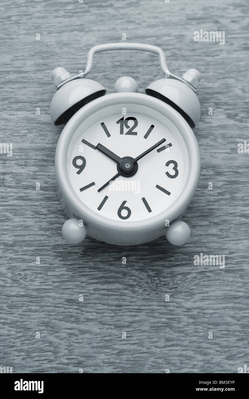 small cute alarm clock monochrome photograph on the wooden table - Stock Image