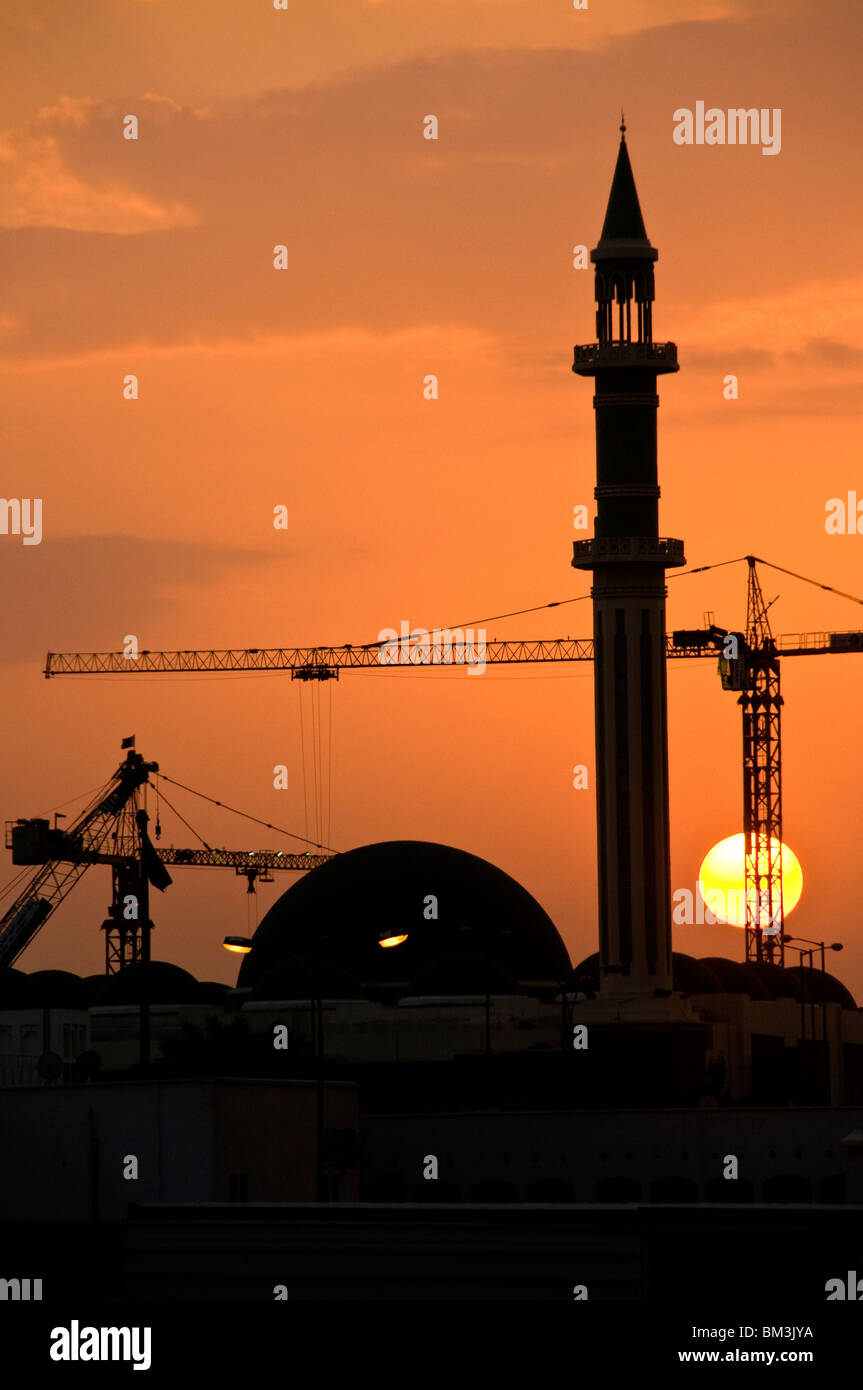 Qatar, Doha, Grand Mosque minaret with construction cranes and setting sun - Stock Image