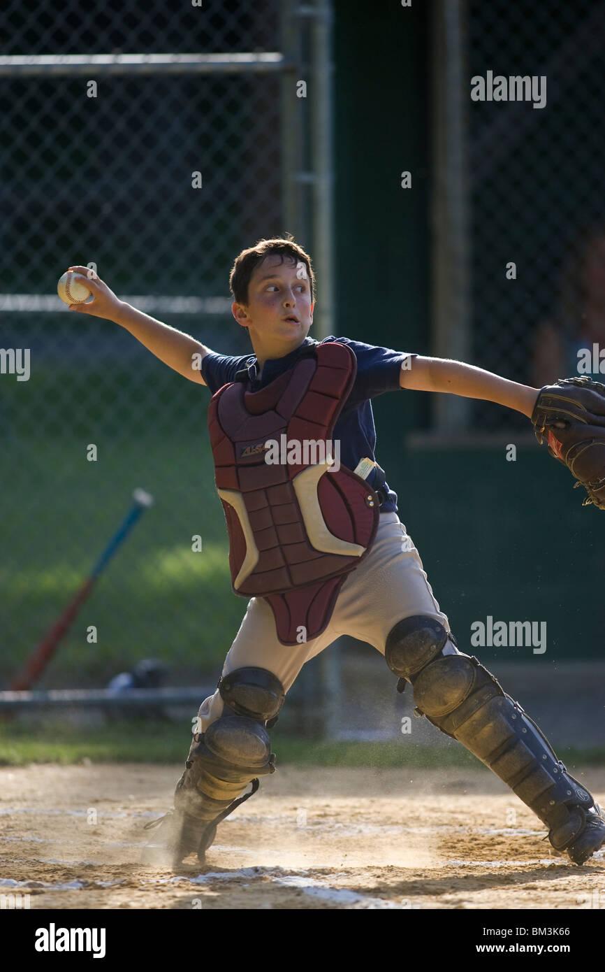 10 year old boy catching during baseball game. - Stock Image