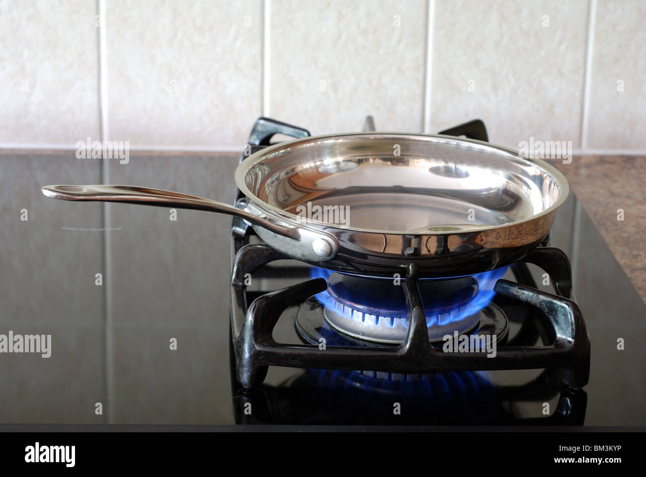 Cooking in a frying pan on a gas stove - Stock Image