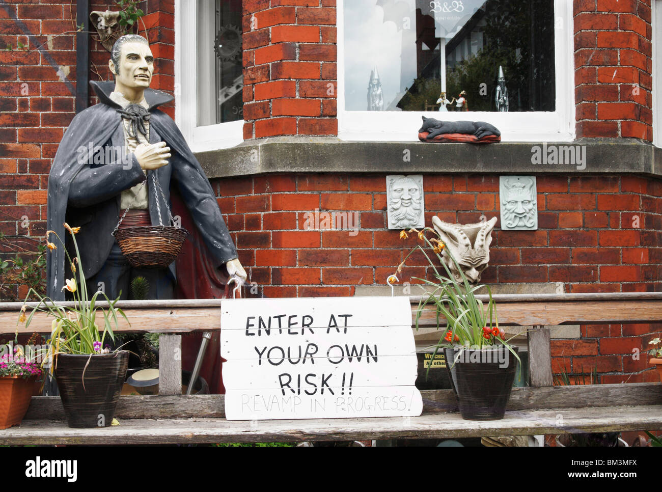 """Statue of Dracula outside Gothic themed bed & breakfast in Whitby. Sign says """"enter at your own risk revamp in progress"""" Stock Photo"""