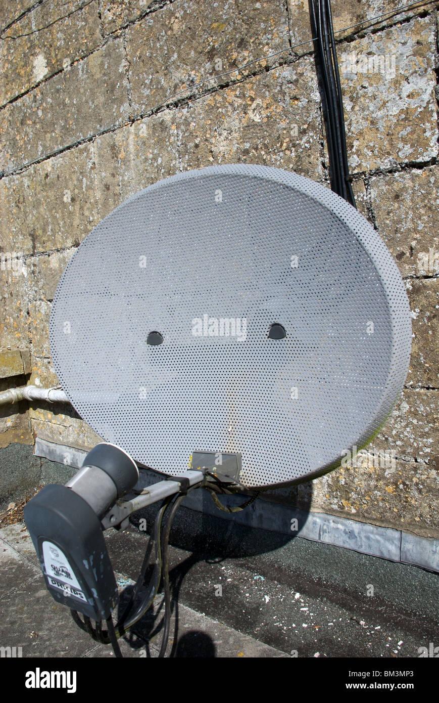 Satellite television dish on house, England, UK - Stock Image