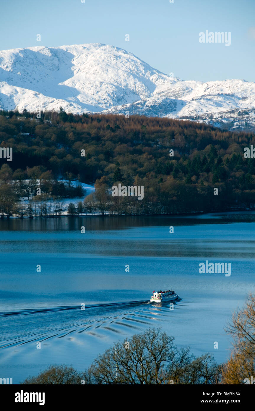 A pleasure boat on Lake Windermere in winter, Lake District, Cumbria, England, UK.  Behind is Wetherlam in the Coniston - Stock Image