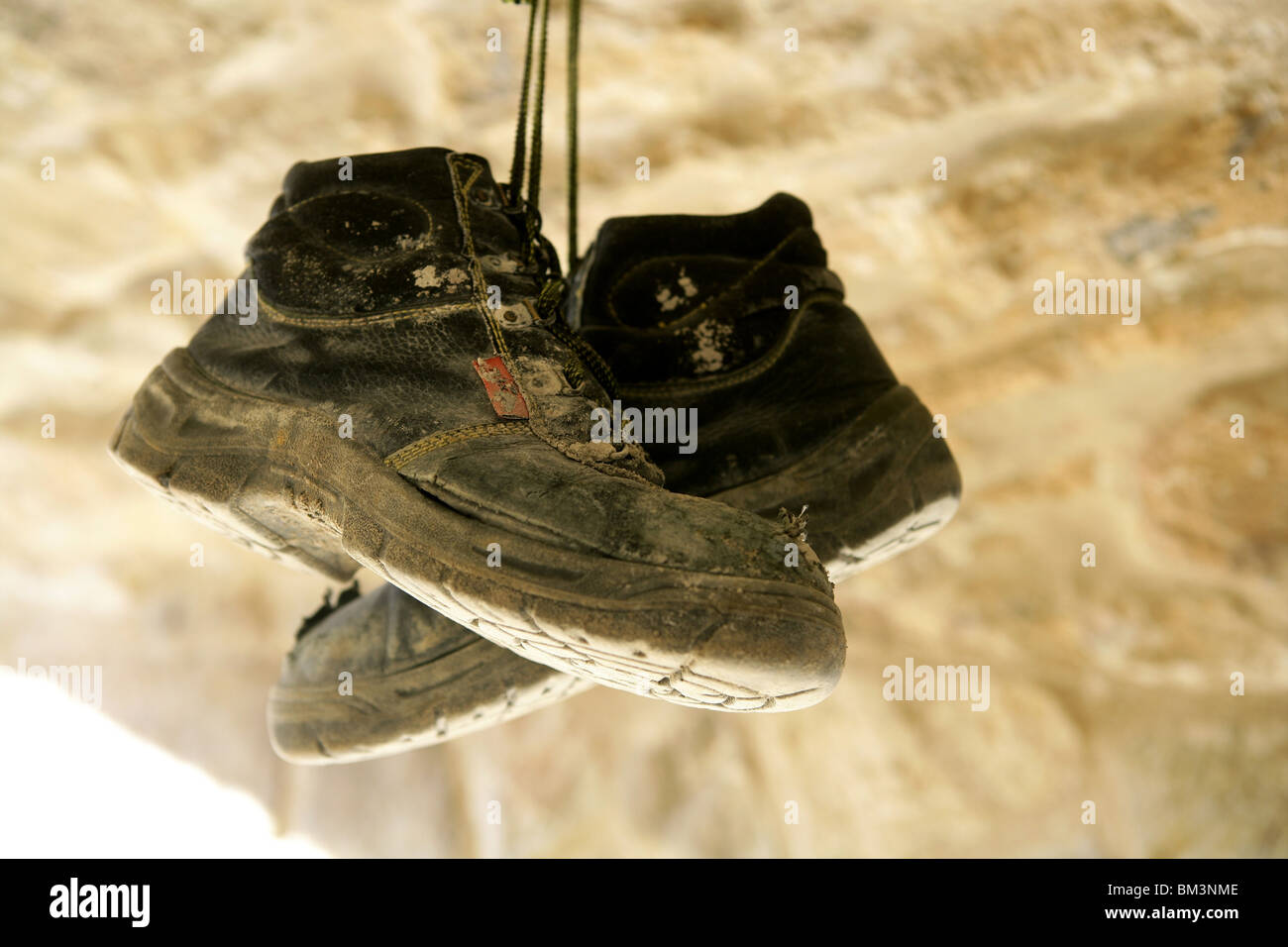 Construction worker left his aged old boots away, hunged on the rocks - Stock Image