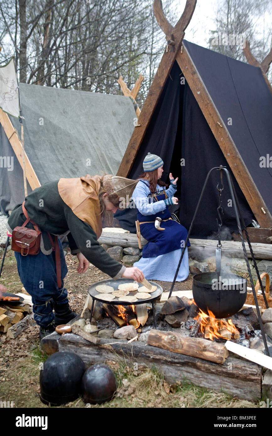 Viking reenactment. Man in Viking robes bakes flatbread on open fire in Viking camp. Ale Viking Village. West Sweden. - Stock Image