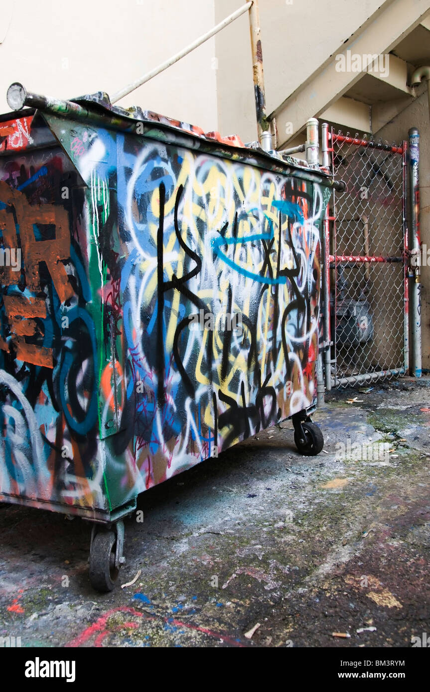Graffiti on dumpster in back alley in downtown Olympia, Washington. - Stock Image