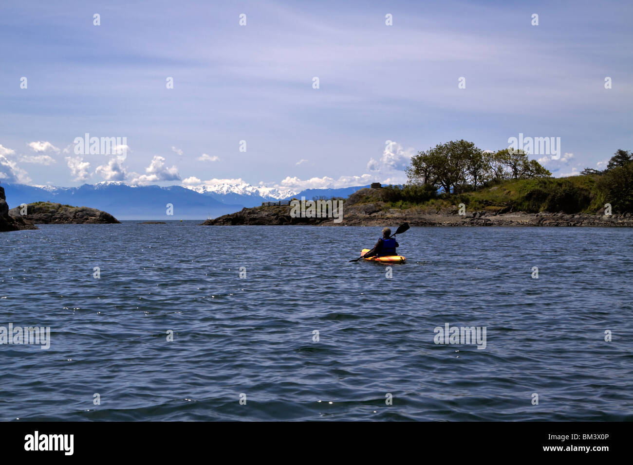 A kayaker paddles towards the 18 mile distant Olympic Mountains in the Middle Harbour, Victoria, British Columbia, - Stock Image