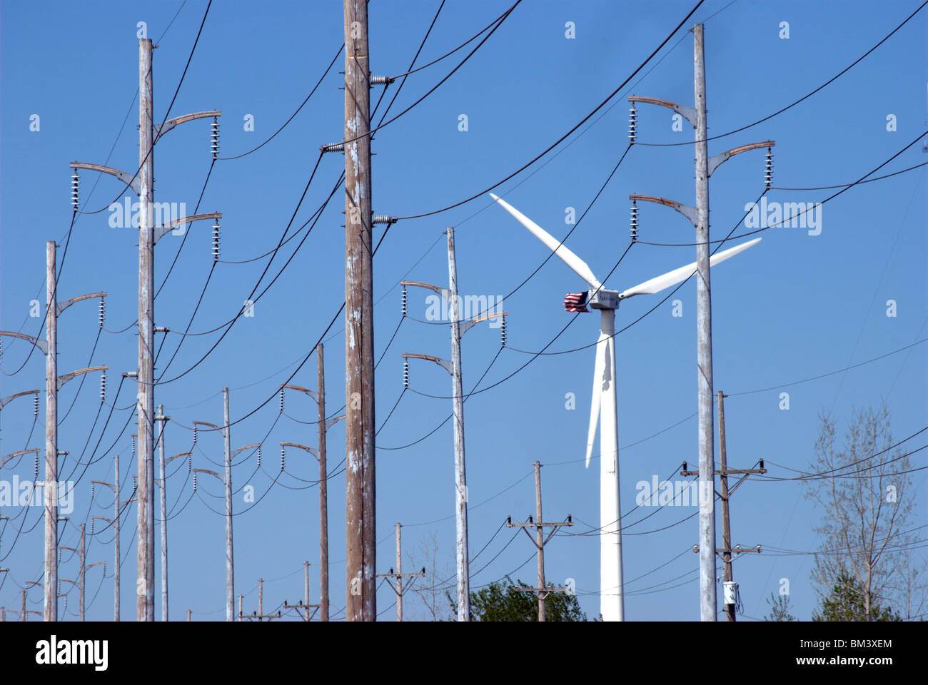 Wind turbine for industrial plant among traditional energy grid lines - Stock Image