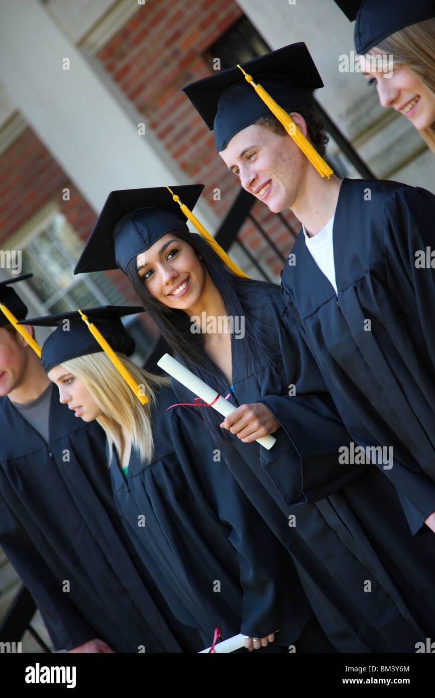 Graduate looking at camera and smiling - Stock Image