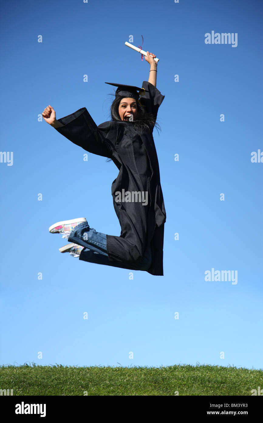 Graduate jumping into air - Stock Image