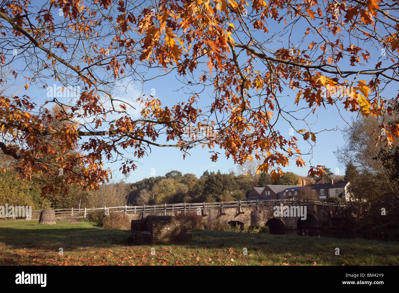 Tilford Surrey England UK. River Wey and medieval old east bridge in historic village in autumn - Stock Image