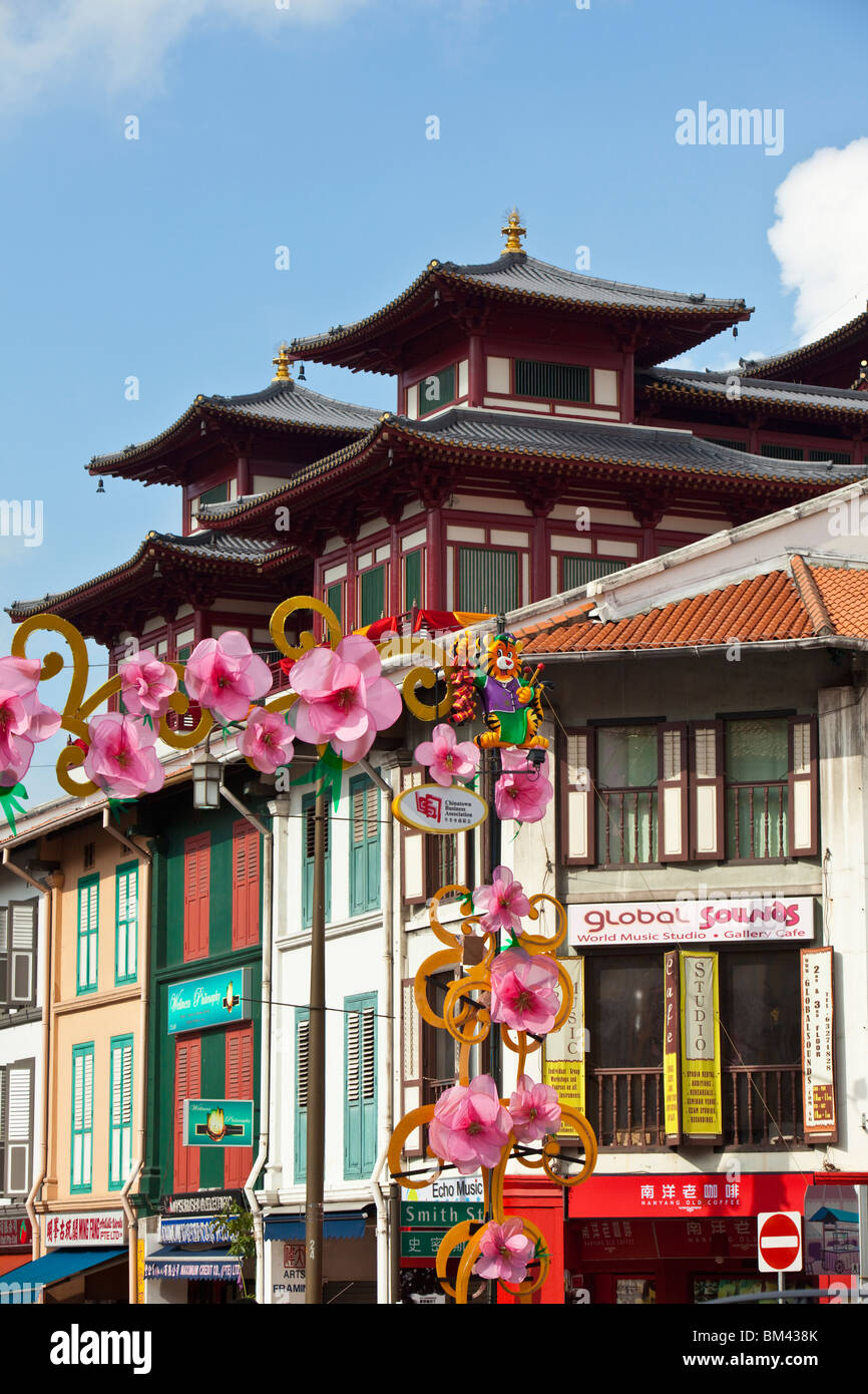 Colourful shophouses with the Buddha Tooth Relic Temple in the background. Chinatown, Singapore - Stock Image