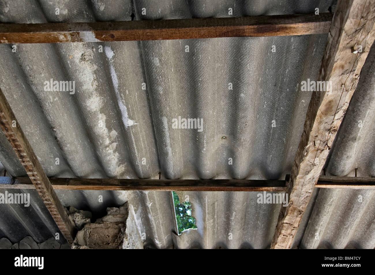 Broken asbestos roofing inside an abandoned house. Hazardous material. - Stock Image