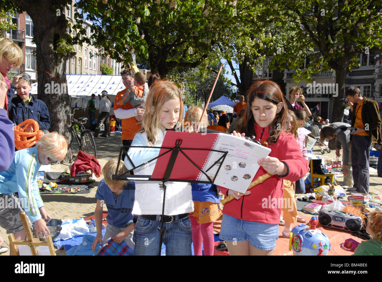 Koninginnedag Amsterdam queensday 30 april crowd festive free market people young two children violin performance - Stock Image