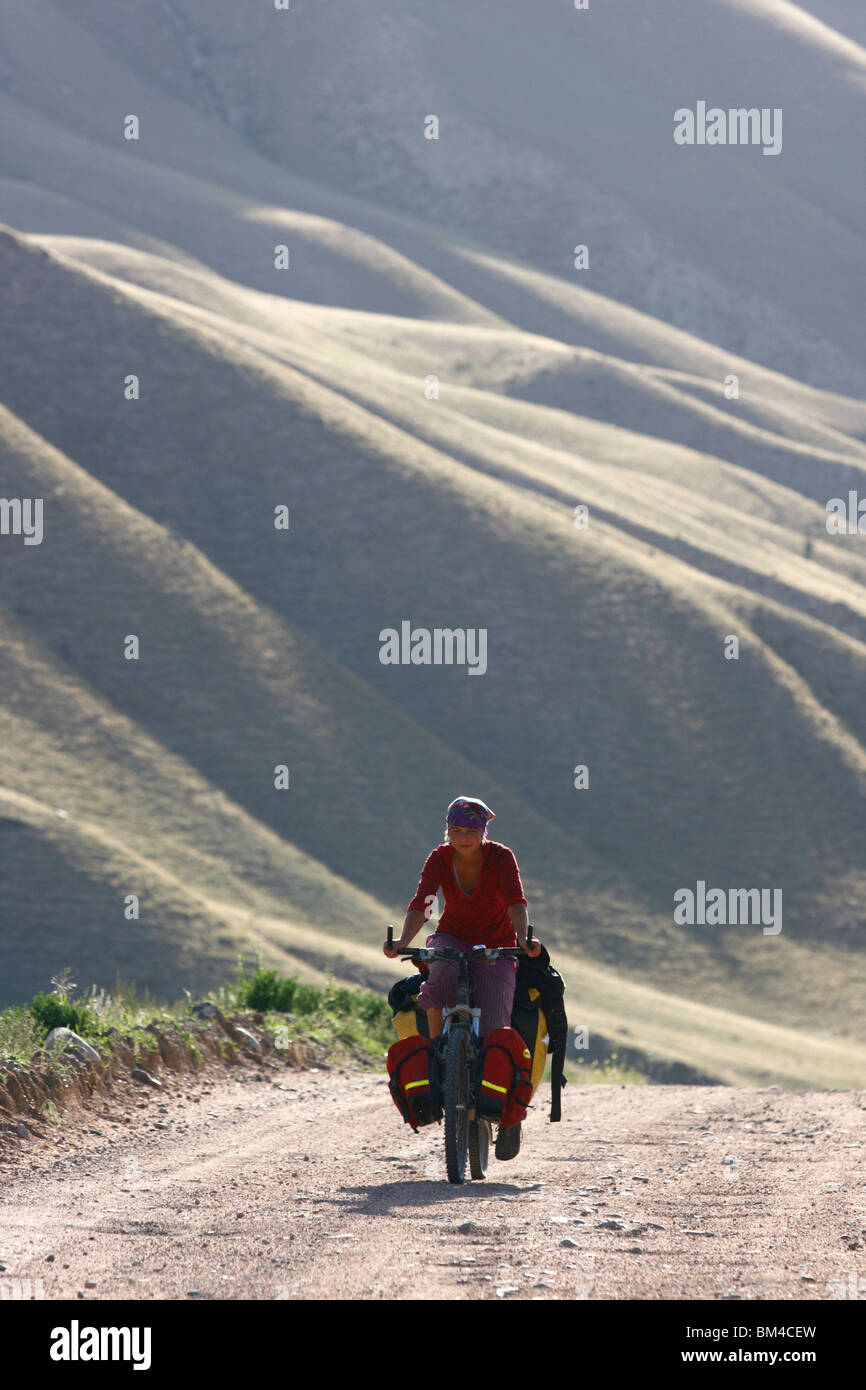 Female cyclist on a mountain road, Kyrgyzstan - Stock Image