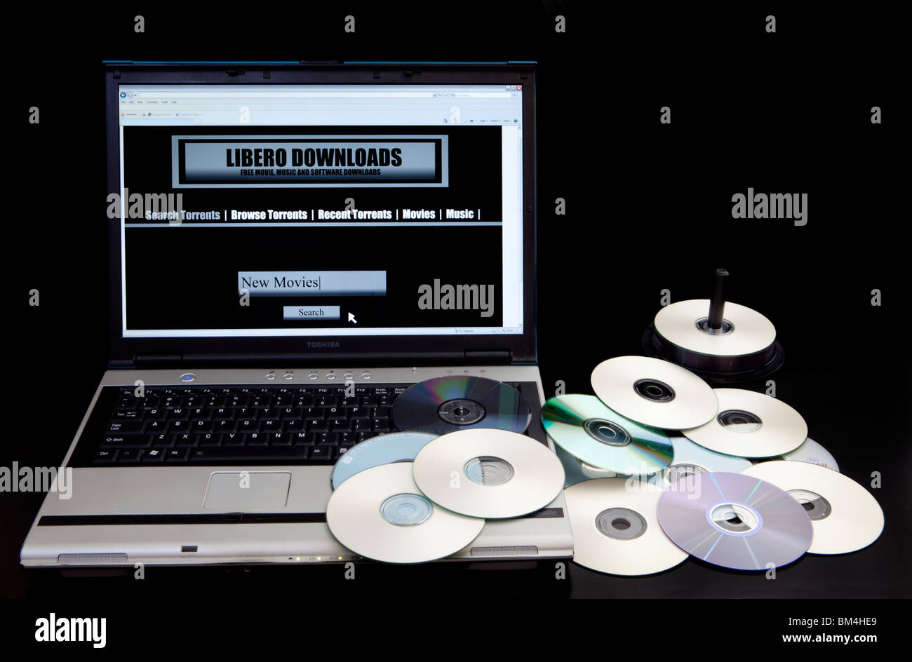 Illegal download website and bittorrent  site on a computer next to a pile of copied DVDs. - Stock Image