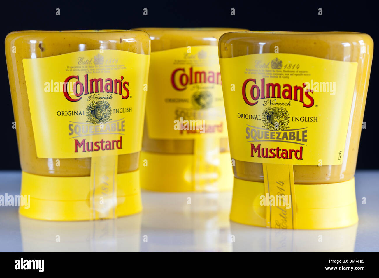 Three containers of Colmans squeezable English mustard - Stock Image